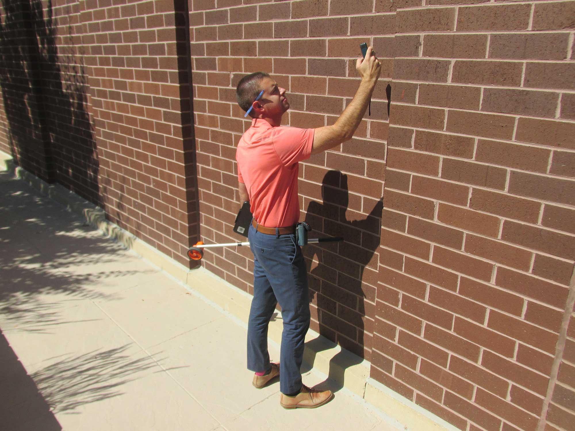 gentleman taking pictures of brick wall