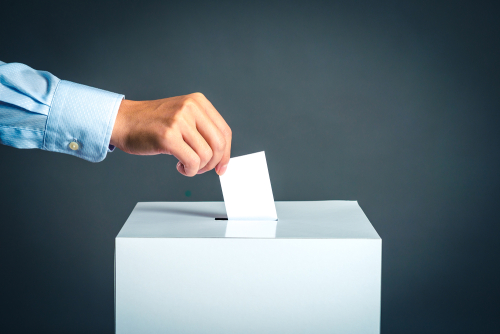 man dropping ballot into election box