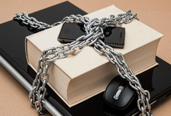 laptop, mouse, phone, and book chained up