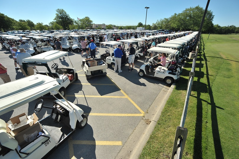 group of golfers and golf carts in parking lot