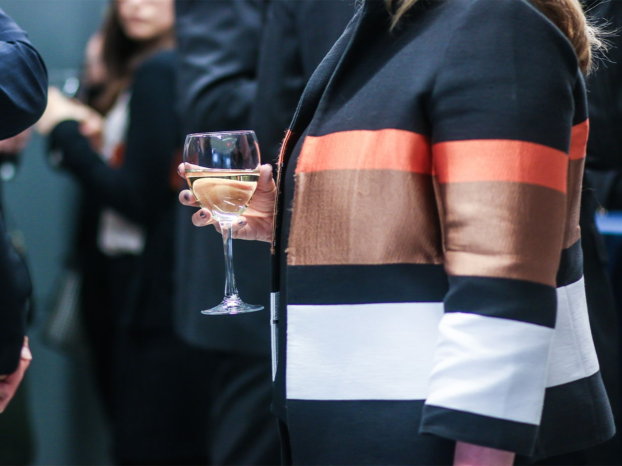 woman with wine glass at networking event