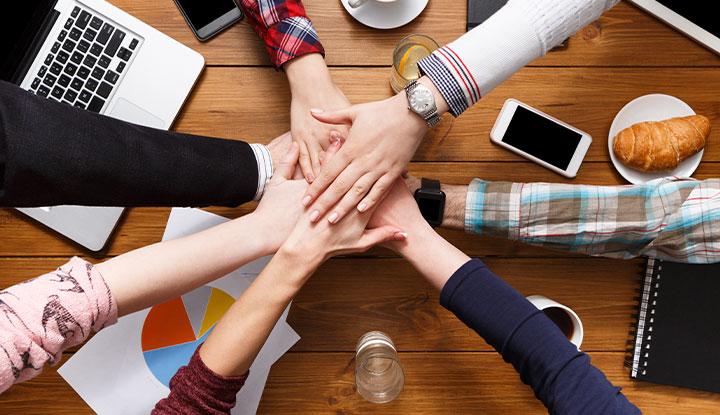 group of business professionals putting hands together