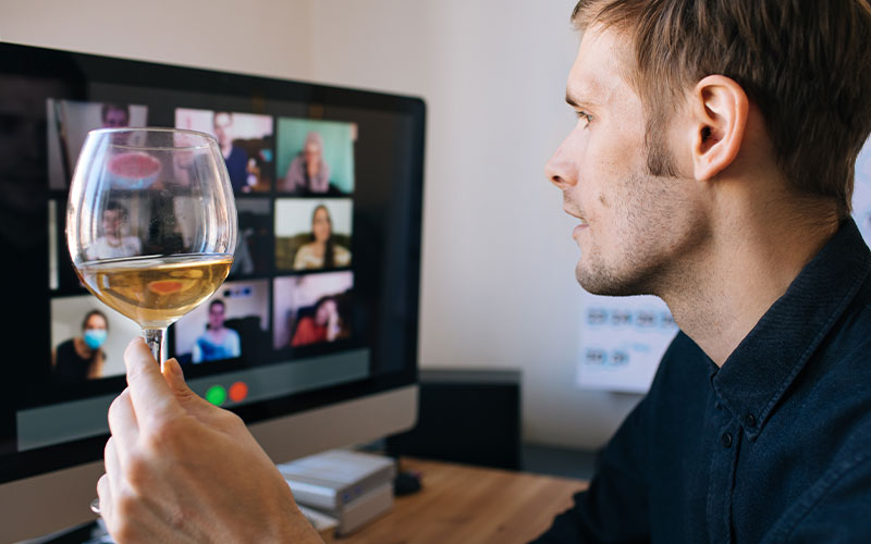 man on zoom call with wine glass