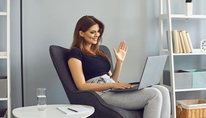 woman waving to laptop
