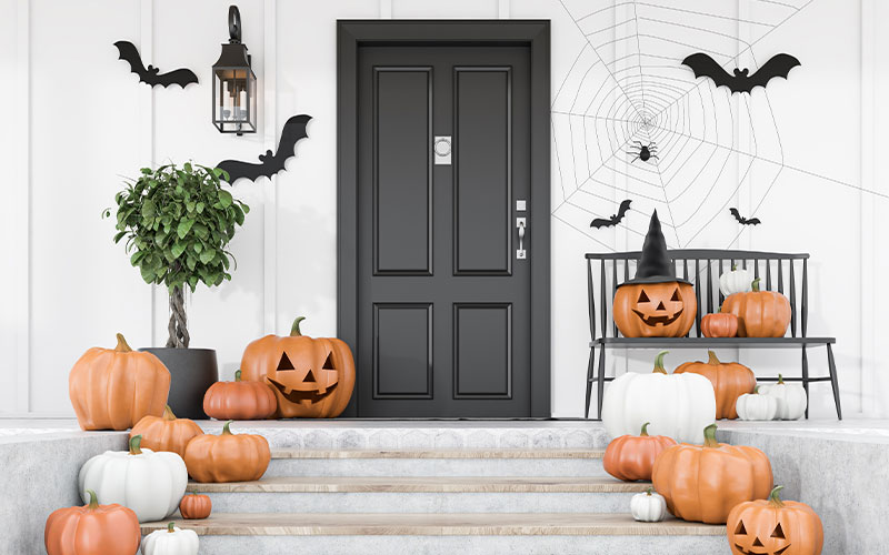 halloween decorations on stoop in front of building entryway