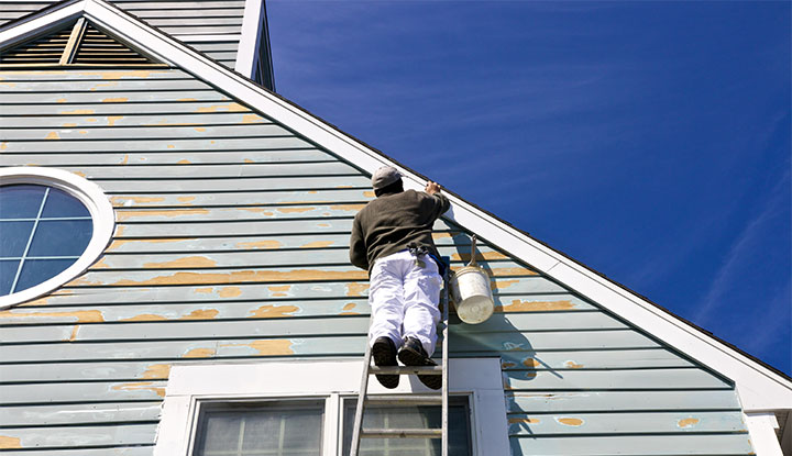 painter touching up exterior of community building