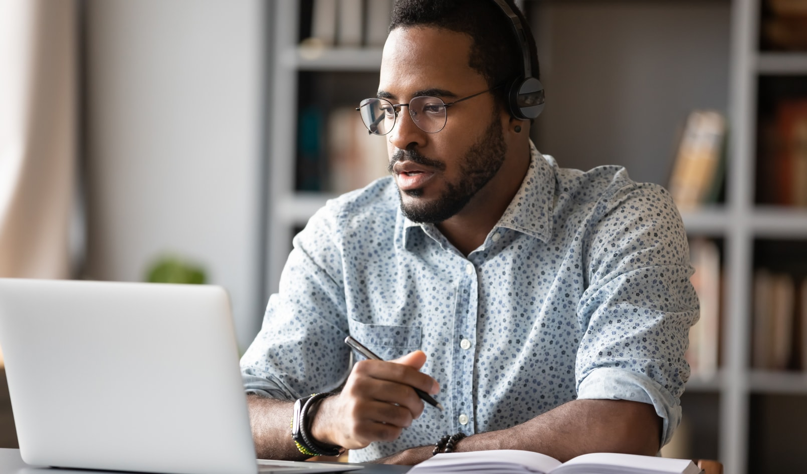 man on headset and working on laptop